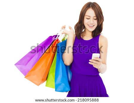 happy young woman holding shopping bags and mobile phone over white background - stock photo