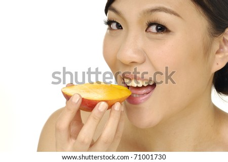 Happy young woman holding sliced mango