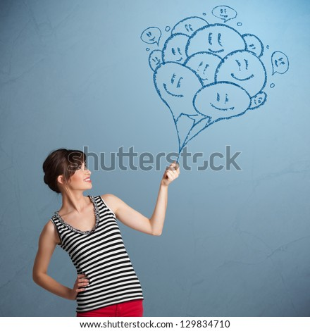 Happy young woman holding smiling balloons drawing - stock photo