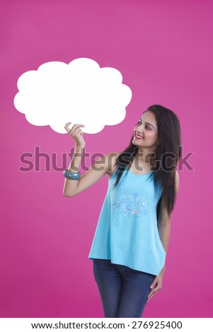 Happy young woman holding thought bubble over pink background