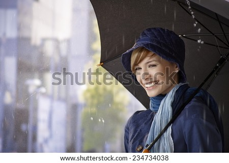 Happy young woman holding umbrella in rain, smiling. - stock photo