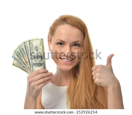 Happy young woman holding up cash money dollars in other compare thinking looking at the corner isolated on a white background - stock photo