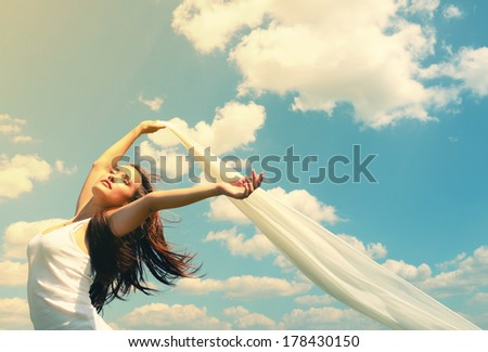 Happy young woman holding white scarf with opened arms expressing freedom, outdoor shot against blue sky. Image toned