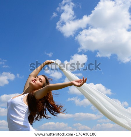 Happy young woman holding white scarf with opened arms expressing freedom, outdoor shot against blue sky. - stock photo