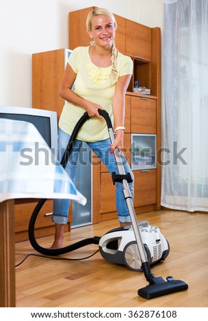 Happy young woman hoovering in living room and smiling