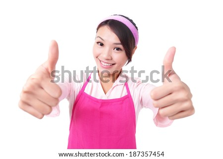 Happy young woman housewife mother wearing kitchen apron and showing thumbs up, asian - stock photo