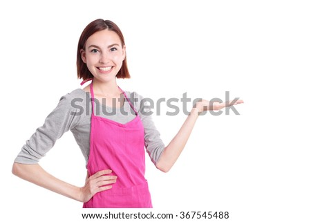 Happy young woman housewife showing something Wearing Kitchen Apron Over White Background, caucasian - stock photo