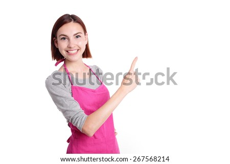 Happy young woman housewife Wearing Kitchen Apron show something isolated Over White Background, caucasian beauty - stock photo