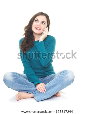 Happy young woman in a blue shirt and blue jeans sitting on the floor. Woman talking on a mobile phone. Isolated on white background
