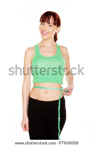 Happy young woman in a green tanktop measures her waist to monitor her weightloss isolated on white