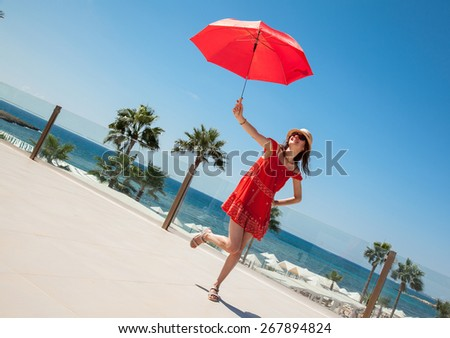 Happy young woman in a red sundress with a red umbrella on seafront background - stock photo
