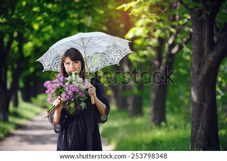 happy young woman in a spring park with an umbrella. - stock photo