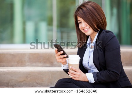 Happy young woman in a suit social networking on her cell phone and drinking coffee