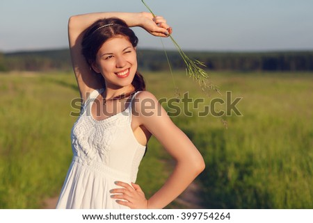 Happy young woman in a white dress walks on summer field.