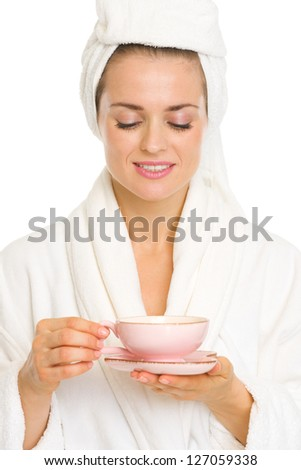Happy young woman in bathrobe enjoying cup of tea