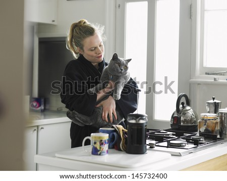 Happy young woman in bathrobe holding cat at domestic kitchen - stock photo