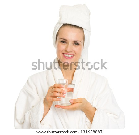 Happy young woman in bathrobe holding glass of water