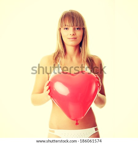 Happy young woman in bikini with heart shaped balloon - valentines concept - stock photo
