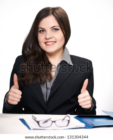 Happy young woman in black jacket sitting at the table. Woman shows a sign okay. On a white background