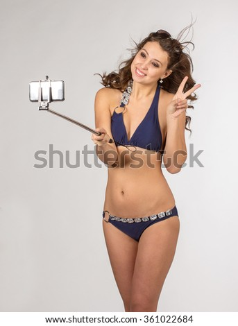 Happy young woman in blue bikini swimsuit taking selfie with smatphone