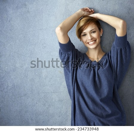 Happy young woman in blue jeans leaning against wall, smiling - stock photo