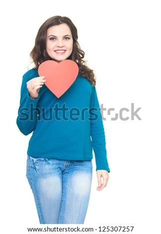 Happy young woman in blue shirt holding red paper heart. Isolated on white background