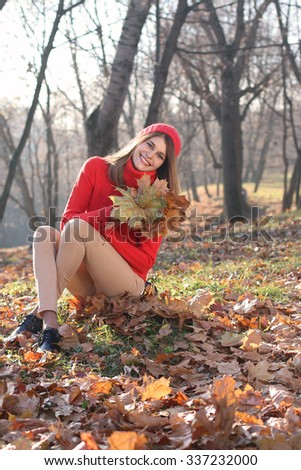 Happy young woman in bright knitwear with autumn leaves in hands