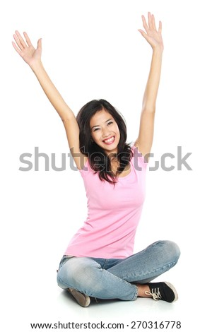 Happy young woman in casual wear sitting with raised arms smiling sitting on the floor. Isolated on white background - stock photo
