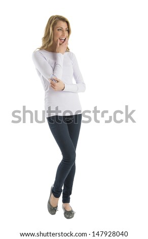 Happy young woman in casuals looking away while standing isolated over white background - stock photo