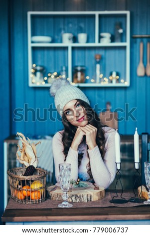 Happy young woman in christmas sitting in kitchen