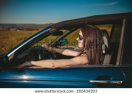 Happy young woman in convertible outdoor