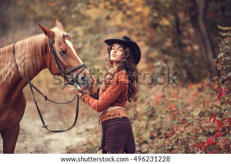 Happy young woman in cowboy hat with her horse at the forest