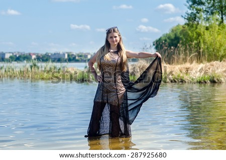 Happy young woman in front of the pond
