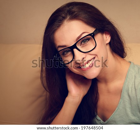 Happy young woman in glasses smiling. Closeup vintage portrait - stock photo