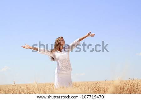 Happy young woman in golden wheat field - stock photo