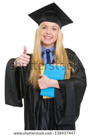 Happy young woman in graduation gown with books showing thumbs up