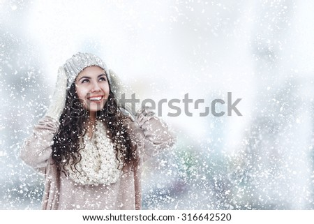 Happy young woman in heat winter sweater and hat