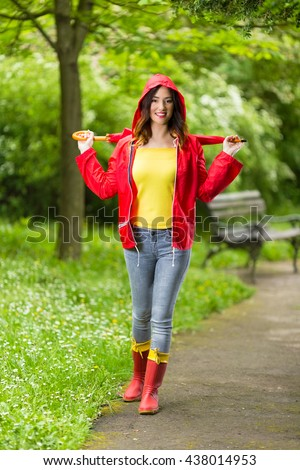 Happy young woman in hooded red raincoat holding red umbrella. She is looking at camera and smiling while walking in the park on a rainy day.