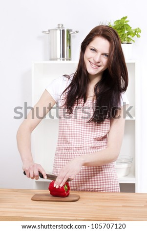 happy young woman in kitchen cutting red paprika for salad - stock photo