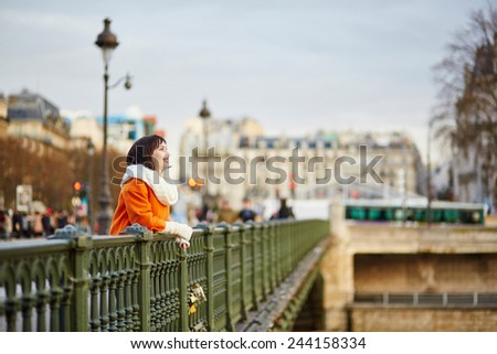 Happy young woman in Paris, standing on a bridge and looking at the Seine - stock photo