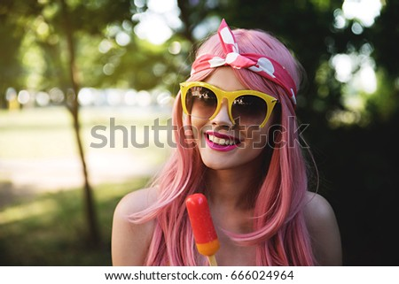 Happy young woman in park holding ice cream
