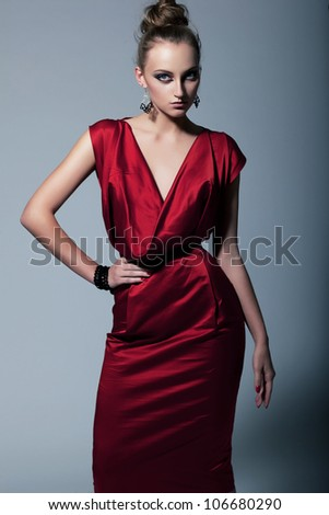 Happy young woman in red dress. Isolated over gray background. - stock photo