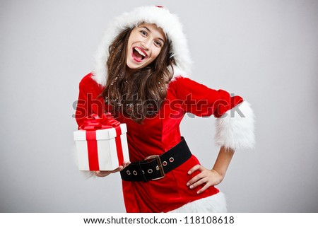 Happy young woman in Santa cloth holding gift box - stock photo
