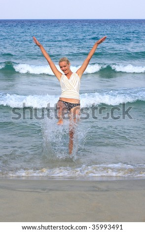Happy young woman in sea splashing water