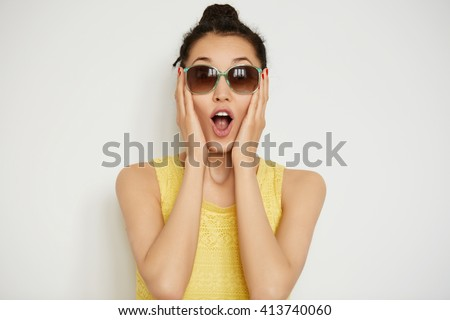 Happy young woman in sunglasses looking surprised at the camera, holding her head in excitement. Close up view of beautiful female posing indoor against white studio background. Body language    - stock photo