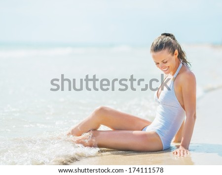 Happy young woman in swimsuit enjoying sitting in sea water - stock photo