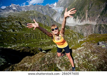 Happy young woman in the mountains against the glacier and blue sky with beautiful clouds. - stock photo