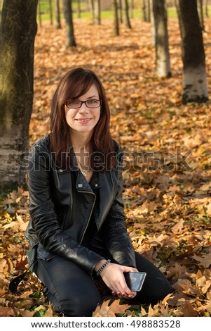 Happy young woman in the park during autumn