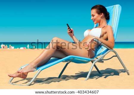 happy young woman in white bikini and sunglasses chatting on her smartphone sitting in deck chair on the sand beach