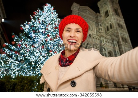 Happy young woman in white coat taking selfie in front of Christmas tree near Duomo in the evening. She having holiday tour and enjoying Christmas decorated historical area of Florence, Italy - stock photo